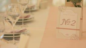 Dettaglio dell'insieme lussuoso della tavola di nozze Numero di ricezione sulla carta sveglia vicino ai vetri ed ai piatti video d archivio