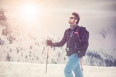 Dettaglio dell'uomo dello sciatore con gli occhiali da sole terra nevosa d'esplorazione che cammina e che scia con lo sci alpino  Immagini Stock