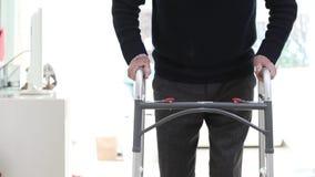 Dettaglio dell'uomo senior che usando struttura di camminata a casa video d archivio