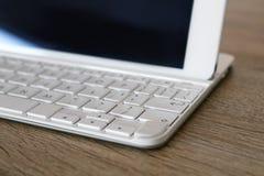 Dettaglio della compressa bianca con la tastiera all'ufficio Fotografia Stock