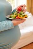 Dettaglio della donna incinta che mangia piatto di insalata sana Fotografia Stock Libera da Diritti
