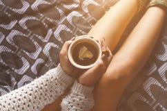 Dettaglio della luce sexy del sole e della giovane donna La donna tiene una tazza di caffè ed ha letto un libro Immagini Stock