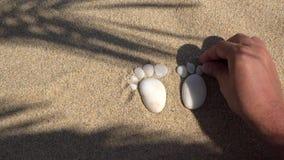 Dettaglio della mano che sistema i piccoli ciottoli bianchi sotto forma di una sogliola del piede sulla sabbia fine della spiaggi stock footage