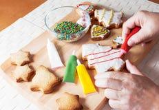 Dettaglio della mano di una donna che sta decorando il biscotto di Natale Fotografia Stock Libera da Diritti