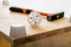 Dettaglio della mobilia della plastica e del martello sul modulo di legno Immagine Stock