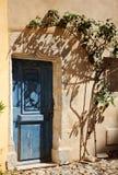 Dettaglio della parete ocracea della casa con la porta blu dentro e l'albero dell'ombra immagine stock