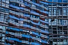 Dettaglio della riflessione di un edificio residenziale su una parete di vetro del centro commerciale Immagini Stock Libere da Diritti