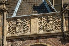 Dettaglio della scultura della pietra di altorilievo della stemma nella vecchia facciata della chiesa di Amsterdam fotografia stock libera da diritti