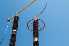 Dettaglio della sottostazione elettrica, isolamento ad alta tensione rosso sopra la SK blu immagini stock libere da diritti