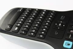 Dettaglio della tastiera di QWERTY compatta sul dispositivo di stampante tenuto in mano dell'etichetta, fondo bianco Fotografia Stock