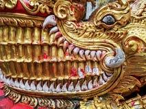 Dettaglio della testa dorata del drago del Naga con i grandi denti bianchi fotografie stock libere da diritti