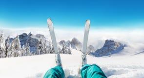 Dettaglio delle gambe alpine dello sciatore, guardante il panorama della valle Immagine Stock
