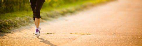 Dettaglio delle gambe di un corridore femminile sulla strada Fotografie Stock