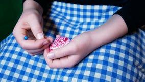 Dettaglio delle mani della ragazza, che incide gli ornamenti di Pasqua sulle uova colorate, con l'incisione della tecnica, abitud video d archivio