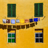 Dettaglio delle pareti gialle variopinte, delle finestre e dei vestiti della casa Fotografia Stock Libera da Diritti