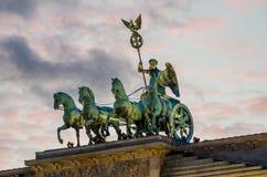 Dettaglio delle sculture sopra il tor di Brandenburger a Berlino con la luce rosa di sera e le nuvole molli, Germania Fotografia Stock
