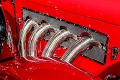 Dettaglio dello scarico di Chrome che esce dal cappuccio di un'automobile prebellica rossa classica antica Immagine Stock