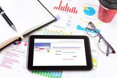 Dettaglio di affari di una compressa che si trova sopra i grafici ed i grafici di affari Immagini Stock