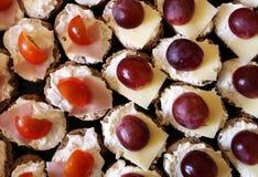 Dettaglio di formaggio saporito con il prosciutto, il pomodoro e l'uva Fotografie Stock Libere da Diritti