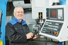 Dettaglio di misurazione del lavoratore dell'industria vicino alla fresatrice di CNC fotografia stock