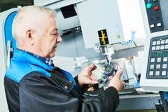 Dettaglio di misurazione del lavoratore dell'industria vicino alla fresatrice di CNC immagini stock libere da diritti