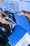 Dettaglio di un artista con l'aerografo che colora un cappello blu Fotografia Stock