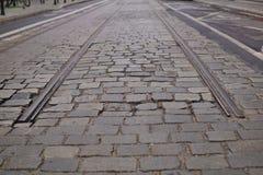 Dettaglio di un'estremità dei binari fra la strada cobbled come simbolo della stazione terminale Immagini Stock