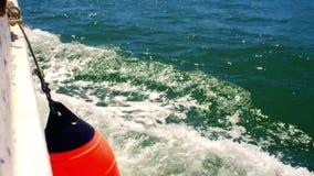 Dettaglio di una barca che tagliato le onde mediterranee delicate fuori dalla costa di Tarragona, Spagna video d archivio