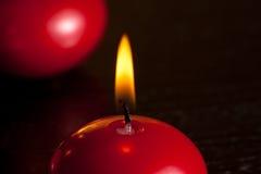 Dettaglio di una candela rossa di natale sul fondo caldo della luce della tinta Fotografia Stock
