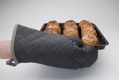 Dettaglio di una mano gloved che porta un vassoio con le mele arrostite immagine stock