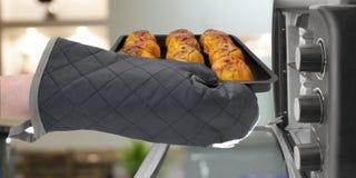 Dettaglio di una mano gloved che prende fuori in un forno un vassoio con le mele arrostite fotografia stock