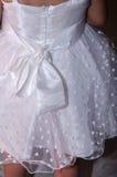 Dettaglio di una ragazza bianca del vestito con un arco sui cuori posteriori e bianchi Fotografie Stock Libere da Diritti