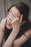 Dettaglio di una ragazza che nasconde il suo fronte Fotografia Stock