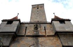 Dettaglio di vecchia costruzione con la maschera di pietra e di vecchia torre nella città di Rothenburg in Germania Immagine Stock