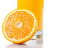 Dettaglio di vetro pieno di succo d'arancia vicino ad a metà arancio con spazio per testo immagini stock