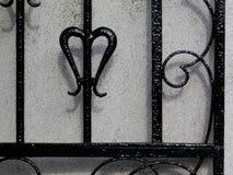 Dettaglio nero del portone del ferro battuto contro la parete bianca dello stucco fotografie stock