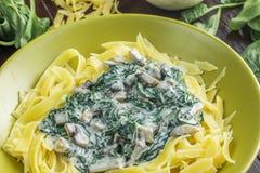 Dettaglio su pasta con i funghi degli spinaci, della crema e del fungo prataiolo sopra Fotografia Stock Libera da Diritti