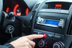 Dettaglio sul cruscotto dell'automobile, dito dell'uomo che preme la luce di emergenza fotografia stock