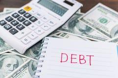 Deuda en nota con la calculadora en fondo del billete de dólar Foto de archivo libre de regalías