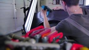 Deukverwijderprogramma's De kerel richt een deuk in de auto op PDR hulpmiddelen Geleide lamp, autoreparatiewerkplaats, zorgvuldig stock footage