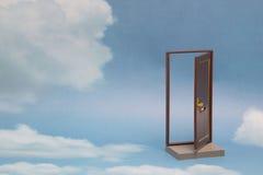 Deur aan nieuwe wereld Open deur op blauwe zonnige hemel met pluizige wolken Stock Foto