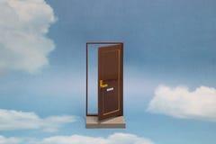 Deur aan nieuwe wereld Open deur op blauwe zonnige hemel met pluizige wolken Stock Fotografie