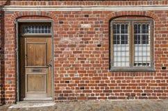 Deur en venster op rode bakstenen muur stock foto