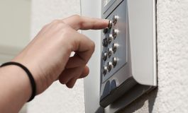 Deur numeriek coderend apparaat op het gebouw, met vrouwelijke hand royalty-vrije stock afbeelding