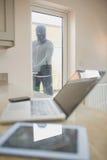Deur van de inbreker de openingskeuken en het bekijken laptop Royalty-vrije Stock Foto's