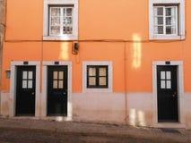 DEUREN EN VENSTERS OP ORANJE VOORGEVEL, LISSABON, PORTUGAL Stock Fotografie
