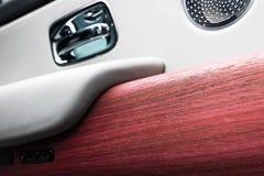 Deurhandvat met de controleknopen van het Machtsvenster van een luxepersonenauto Wit geperforeerd leerbinnenland met het stikken  royalty-vrije stock foto