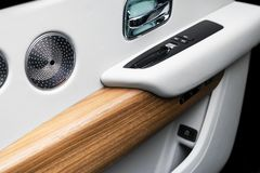 Deurhandvat met de controleknopen van het Machtsvenster van een luxepersonenauto Wit geperforeerd leerbinnenland met het stikken  stock afbeelding