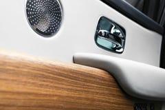 Deurhandvat met de controleknopen van het Machtsvenster van een luxepersonenauto Wit geperforeerd leerbinnenland met het stikken  royalty-vrije stock fotografie