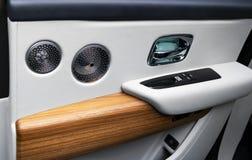 Deurhandvat met de controleknopen van het Machtsvenster van een luxepersonenauto Wit geperforeerd leerbinnenland met het stikken  stock foto